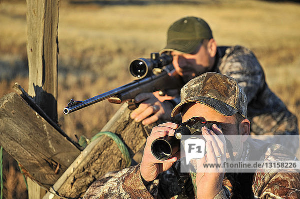 Two deer hunters with rifle and binoculars  John Day  Oregon  USA