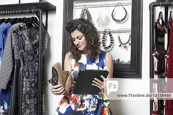 Retail assistant in clothes shop  holding pair of shoes and digital tablet