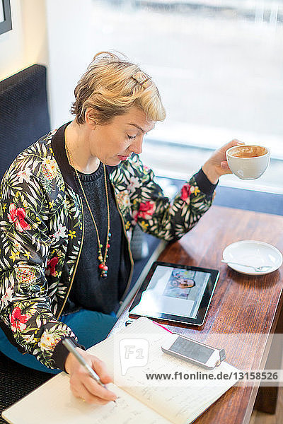 Woman making video call writing in notepad in cafe