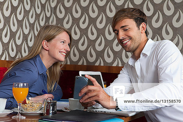Smiling couple using cell phone in cafe