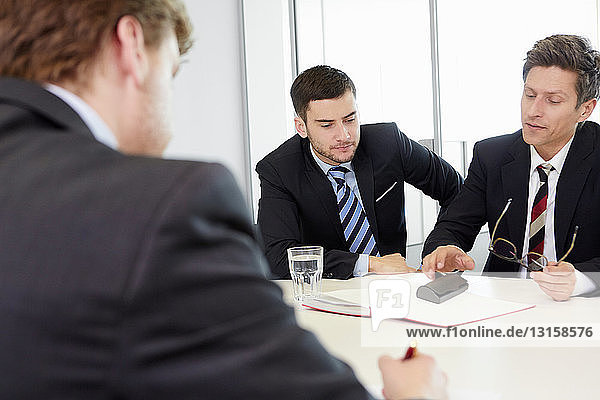 Businessmen sitting around conference table having meeting
