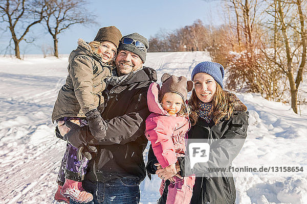 Family smiling together in snow