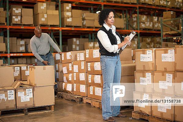 Female warehouse worker holding clipboard