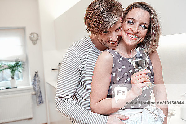 Couple in kitchen  woman holding white wine