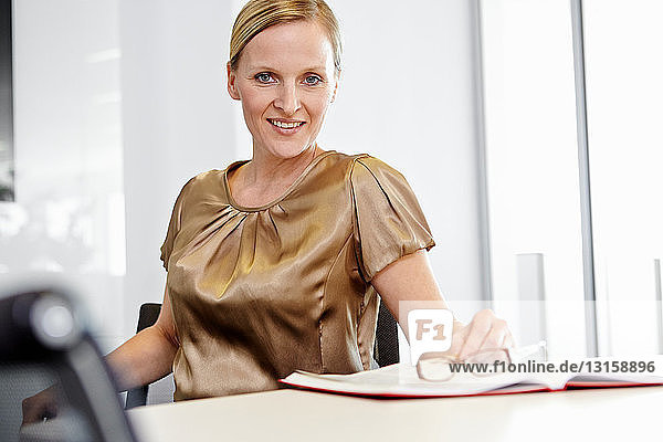 Business woman sitting on office chair  smiling