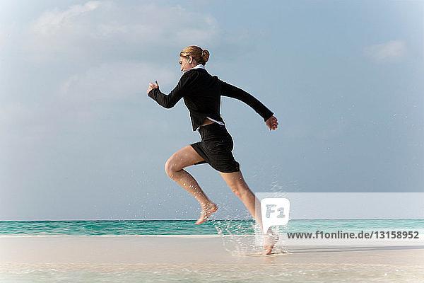 Businesswoman running on tropical beach