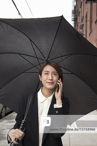 Businesswoman with umbrella  using smartphone on street
