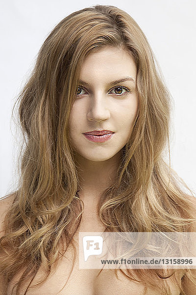 Studio portrait of beautiful young woman with long hair