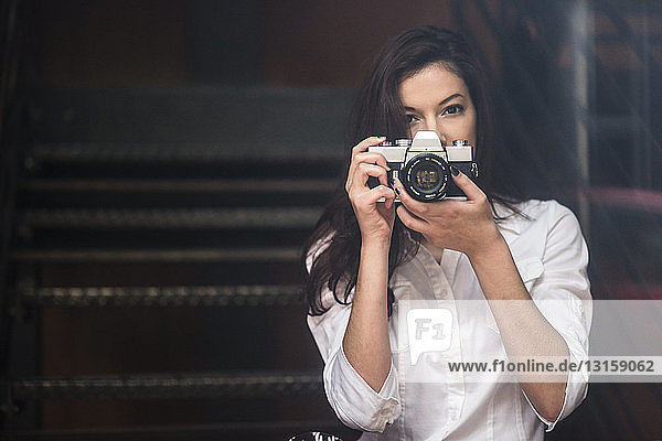 Young woman taking photograph with SLR camera