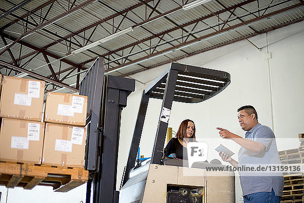 Warehouse workers and forklift truck with boxes