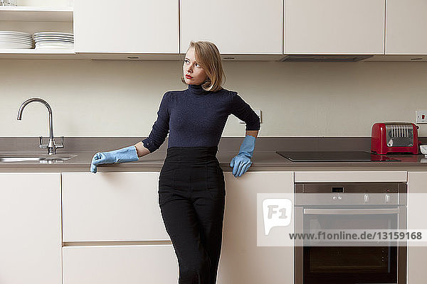 Woman leaning against kitchen cabinet