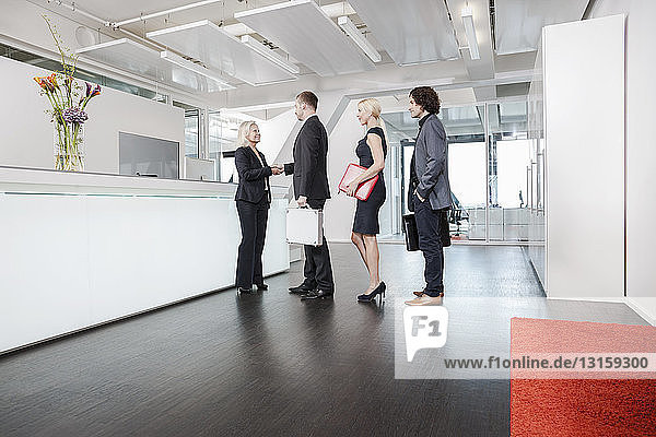 Woman shaking hands with visitors at reception