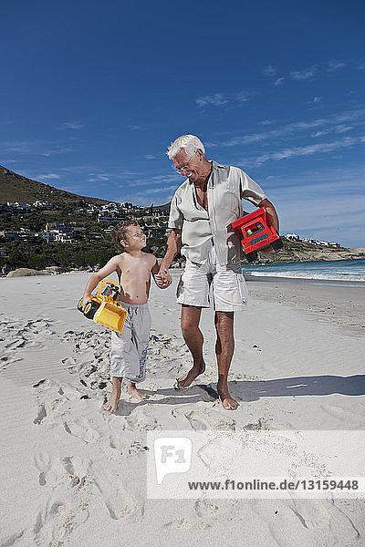 Man holding grandson?s hand on beach