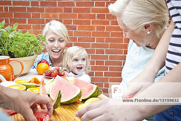 Four women and one female toddler preparing food at garden table