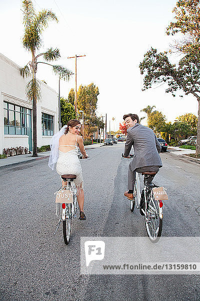 Young newlywed couple cycling along street  rear view