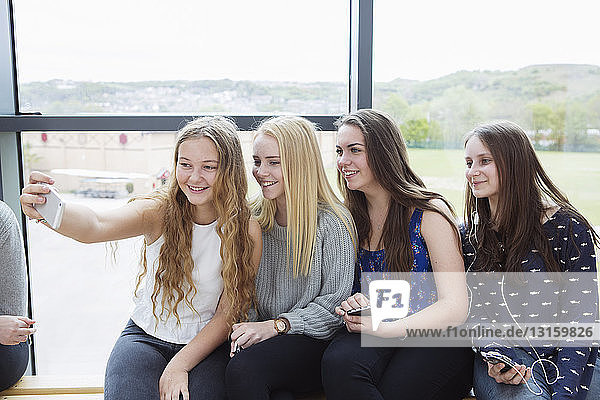 Teenage girls taking selfie with smartphone on bench