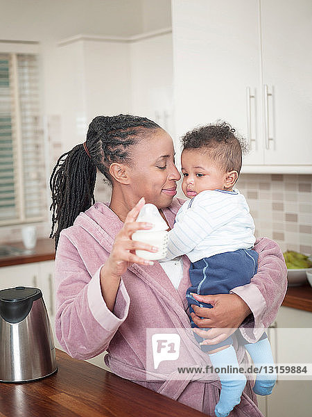 Mother holding baby boy and baby bottle
