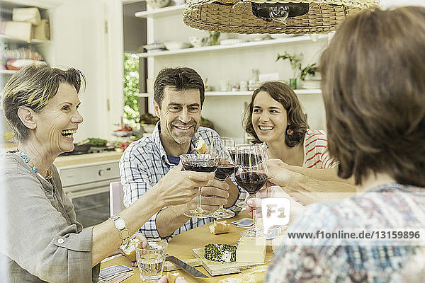 Adult friends making a toast with red wine at dining table