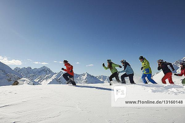 Friends running in snow  Kuhtai  Austria