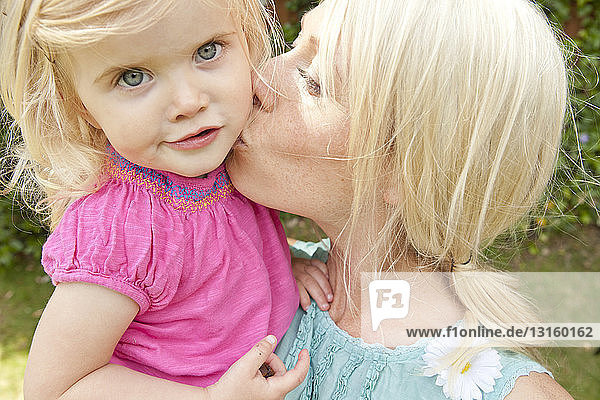 Close up of young adult mother kissing toddler daughter in garden