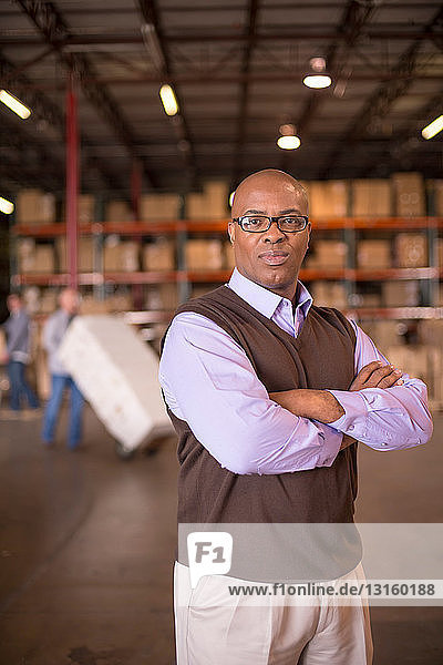 Portrait of warehouse manager with arms folded