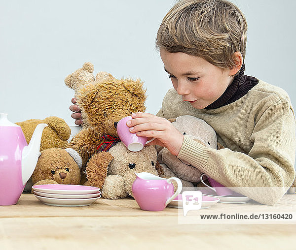 Boy having tea party with teddy bears
