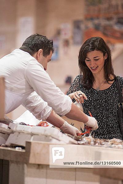 Woman buying fresh fish in market