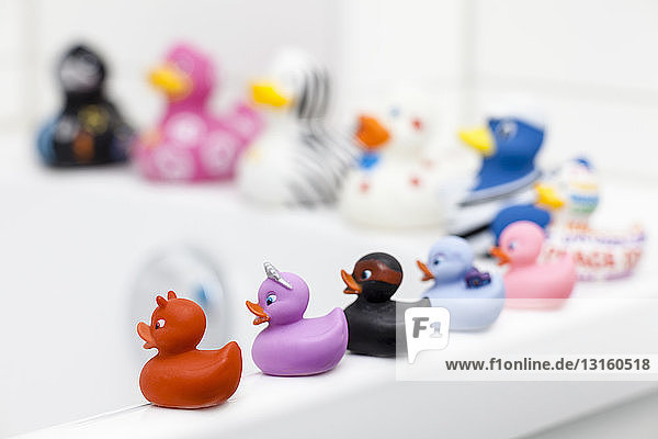 Various rubber ducks sitting on edge of bath