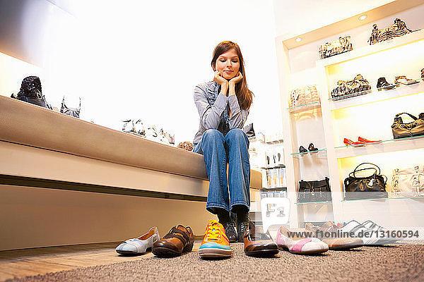 Girl choosing shoes in shoe store Girl choosing shoes in shoe store