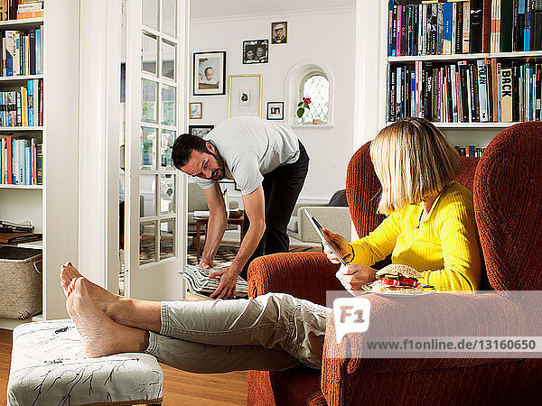 Mature man tidying as woman sits in armchair