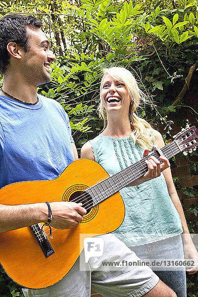 Young man playing acoustic guitar in garden for girlfriend