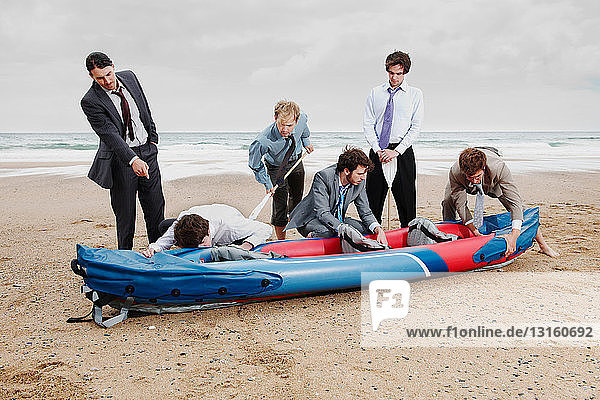 Businessmen with canoe on beach