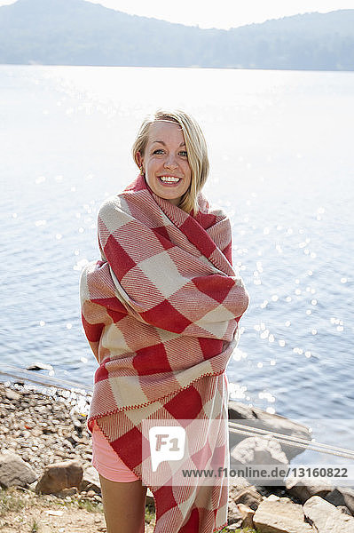 Young woman wrapped in blanket by lake  Hadley  New York  USA