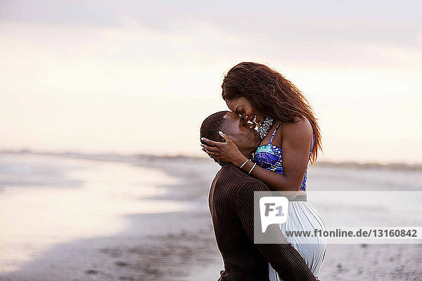 Couple on beach  hugging  face to face