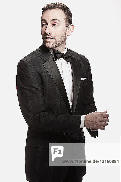 Man in tuxedo standing against white background