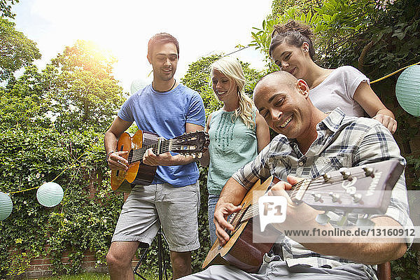 Male friends playing acoustic guitar in garden for girlfriends