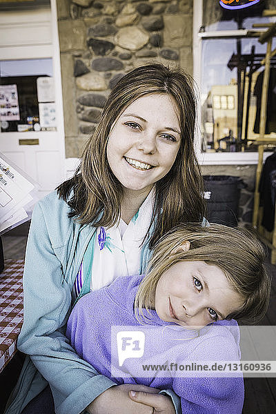 Young woman and girl smiling towards camera  portrait