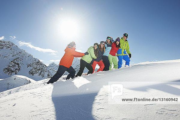Man pushing friends uphill in snow  Kuhtai  Austria
