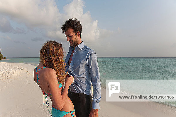 Woman undressing businessman on beach
