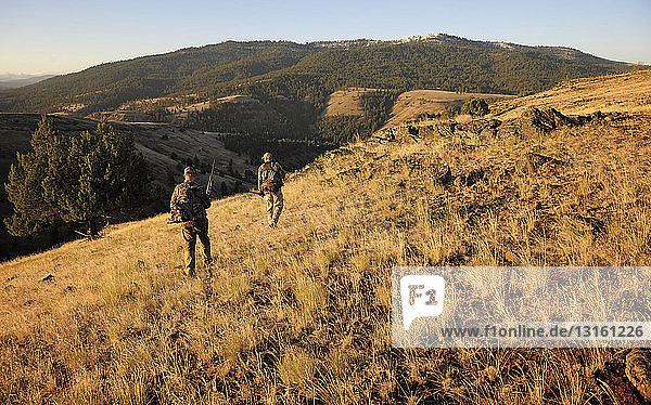 Two deer hunters carrying rifles  John Day  Oregon  USA