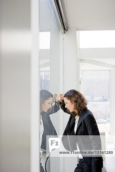 Businesswoman leaning at a glass window