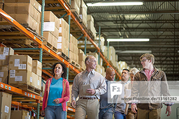 Warehouse workers walking past shelves with boxes