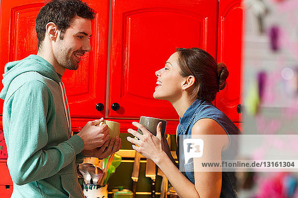 Young couple in kitchen with coffee cups