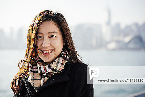 Portrait of young woman wearing checked scarf in front of water  looking at camera smiling
