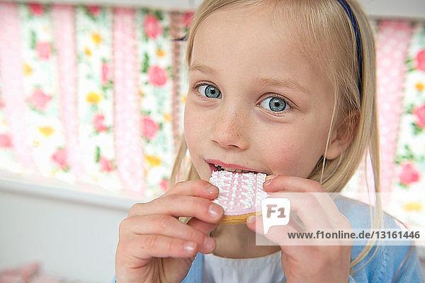 Portrait of young girl eating biscuit in caravan