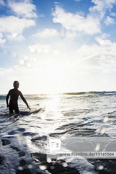 Boy in sea with surfboard  Encinitas  California  USA