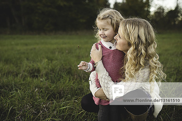Mid adult woman and daughter holding stem of grass in field