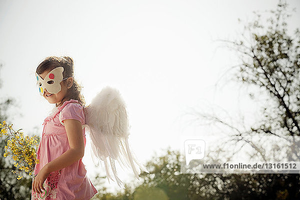 Mädchen mit Engelsflügeln und Gesichtsmaske