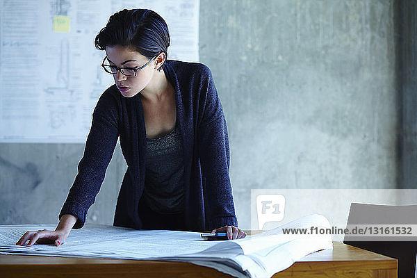 Geschäftsfrau studiert Blaupausen im Büro