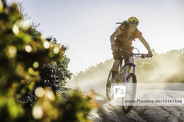 Junge Frau mit dem Mountainbike über Felsen  Monterey  Kalifornien  USA